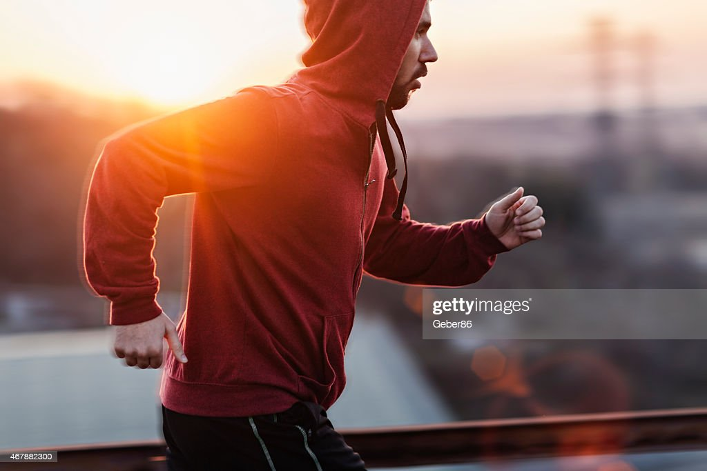 Photo of a man running while sun is setting : Stock Photo