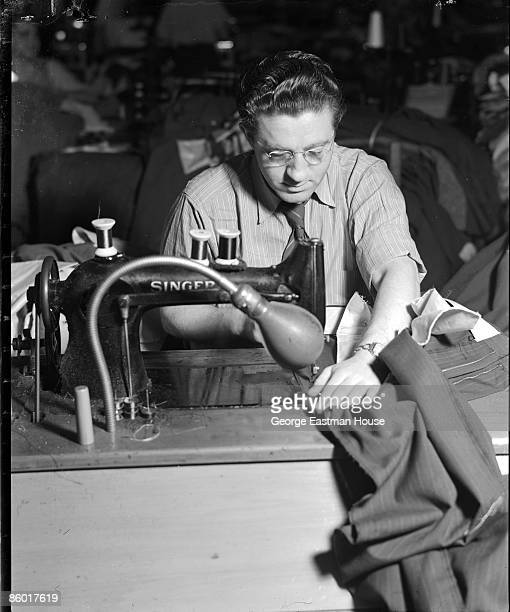 Photo of a man sewing clothing on a Singer sewing machine while at an unidentified clothing factory possibly in New York city ca1930s
