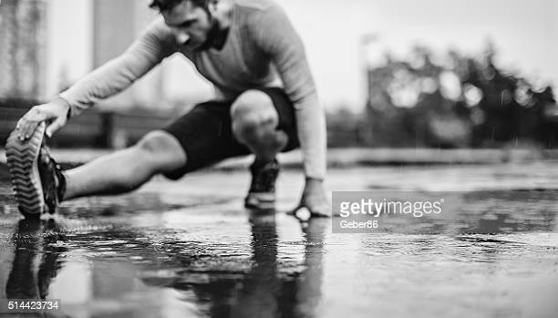 photo of a man stretching in the rain - high contrast stock pictures, royalty-free photos & images