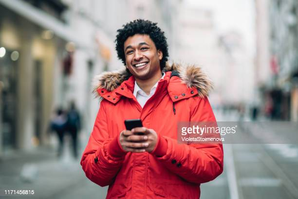 photo of a man using smart phone - red coat stock pictures, royalty-free photos & images