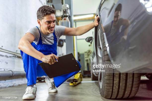 photo of a mechanic at work in his garage - controllo foto e immagini stock