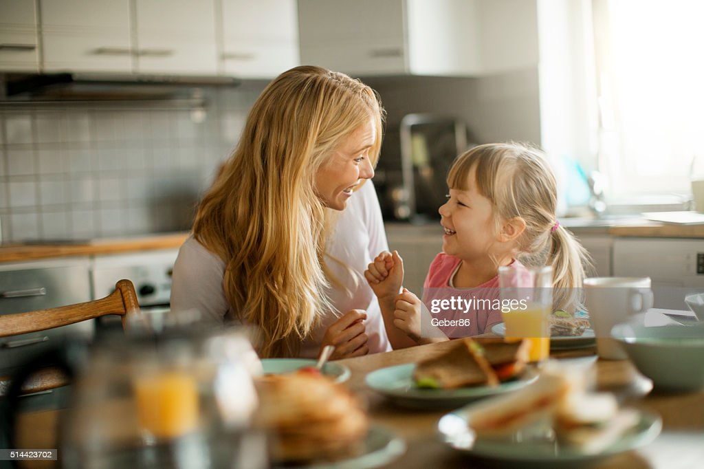 Photo of a mother and daughter having breakfast : Stock Photo