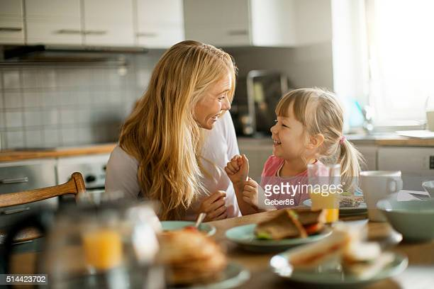 photo of a mother and daughter having breakfast - morgen stockfoto's en -beelden