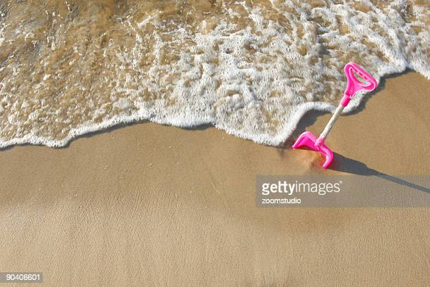 Photo of a pink shovel at the beach
