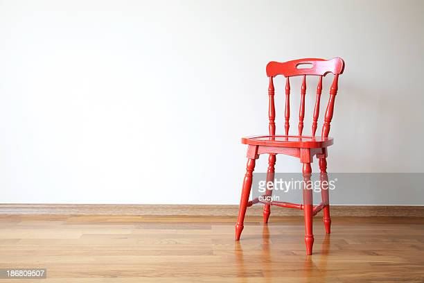Photo of a red wooden chair in front of a blank wall