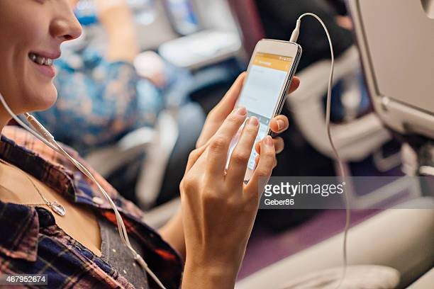 Photo of a smiling woman using smartphone in airplane