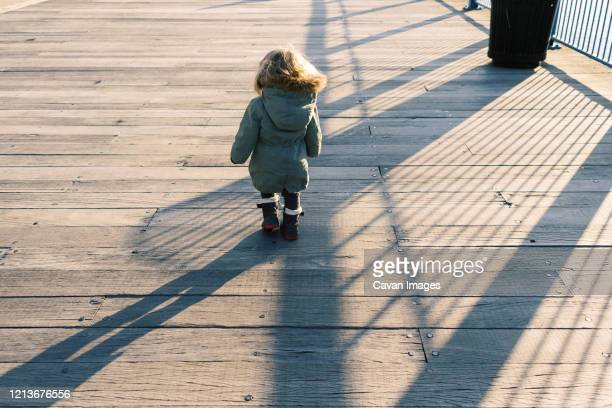 photo of a toddler girl at the boston harbor during a sunset. - toddler at airport stock pictures, royalty-free photos & images
