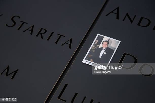 A photo of a victim is left at the North pool during a commemoration ceremony for the victims of the September 11 terrorist attacks at the National...