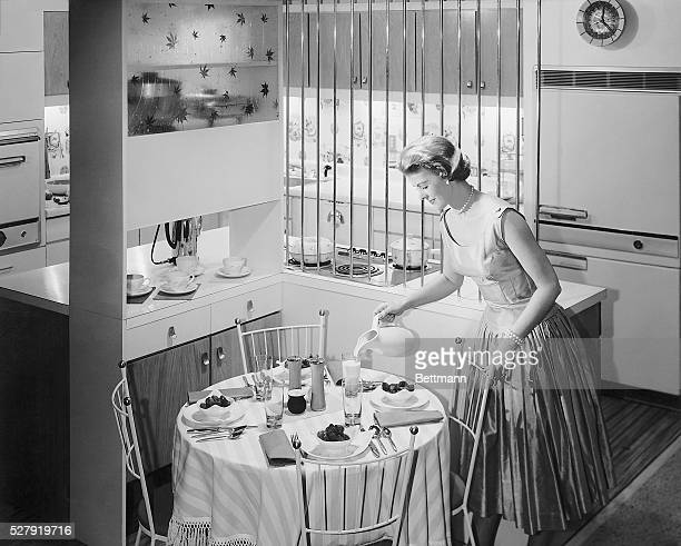 Photo of a woman filling a glass of milk from a pitcher on an already set table The kitchen has the look of a modern 1950s design Circa 1950s