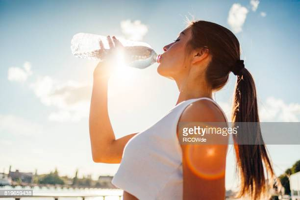 photo of a woman running while sun is setting - refreshment stock pictures, royalty-free photos & images