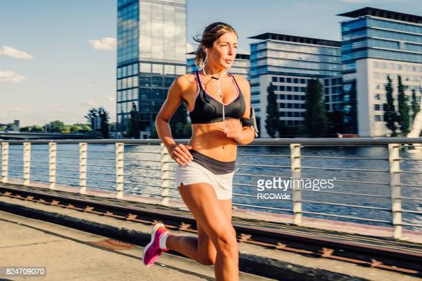 photo of a woman running while sun is setting - running shorts stock pictures, royalty-free photos & images