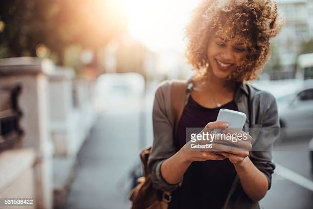 photo of a woman using smart phone - black people laughing stock photos and pictures