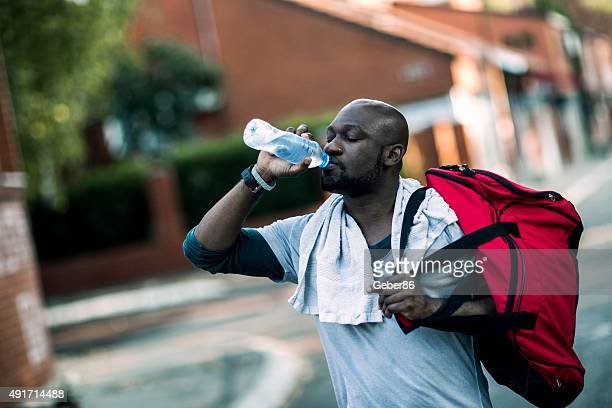 Photo of a young athletic man drinking water