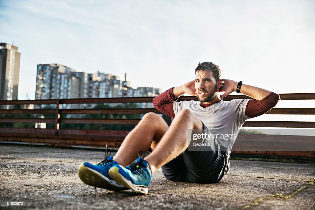 Photo of a young athletic man exercising outdoors : Stock Photo