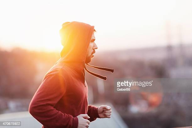 Photo of a young athletic man running outdoors