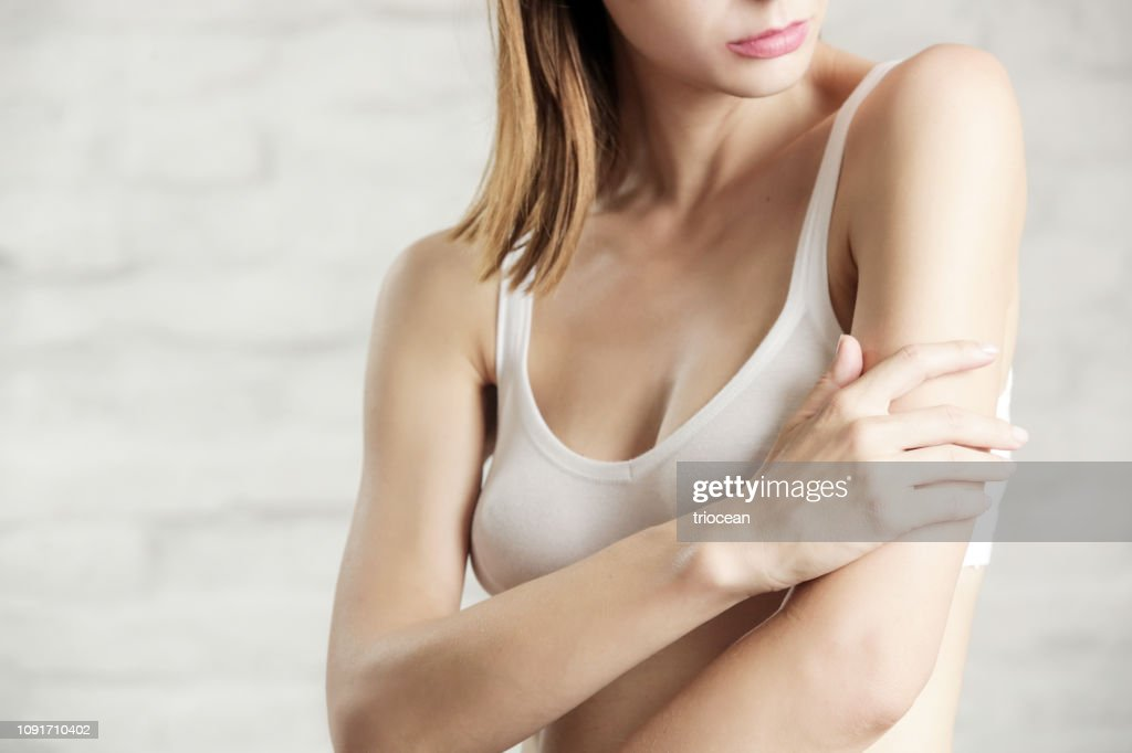 Photo of a young attractive woman touching her arm, dry or dehydrated skincare concept : Stock Photo