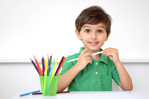 Photo Of A Young Boy With Cup Pencil Crayons