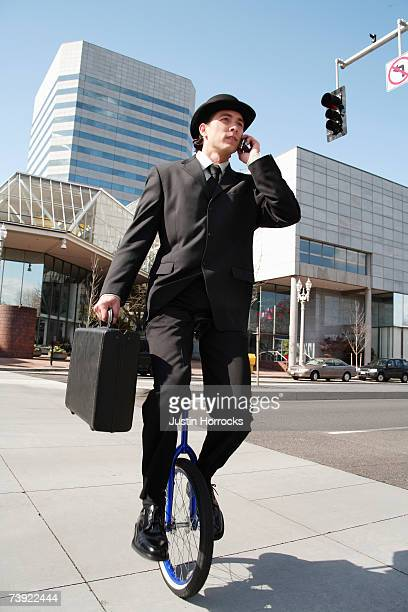 Photo of a young businessman carrying a briefcase and talking on his cell phone while riding a unicycle