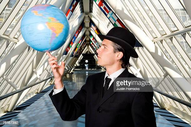 Photo of a young businessman spinning a globe on his fingertip.