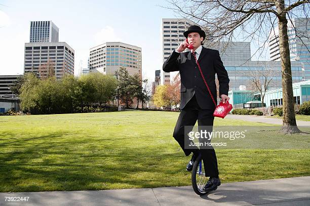 Photo of a young businessman talking on an antiquated red phone while riding a unicycle