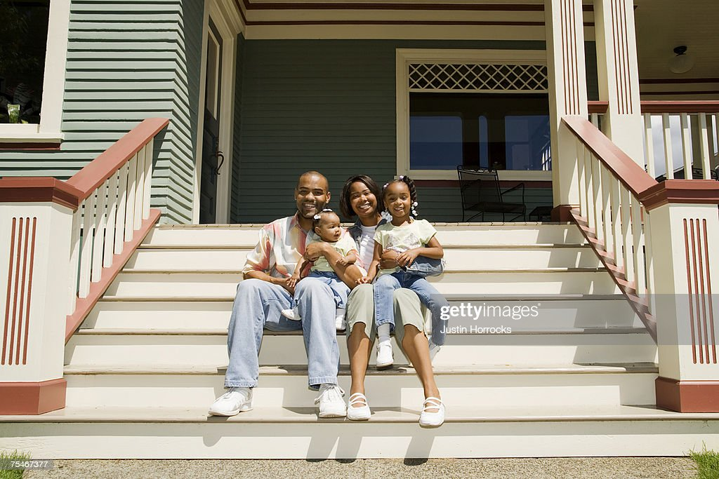 Photo of a young family sitting on the steps in front of their house. : Foto de stock