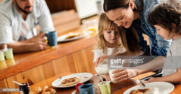 Photo of a young happy family having breakfast