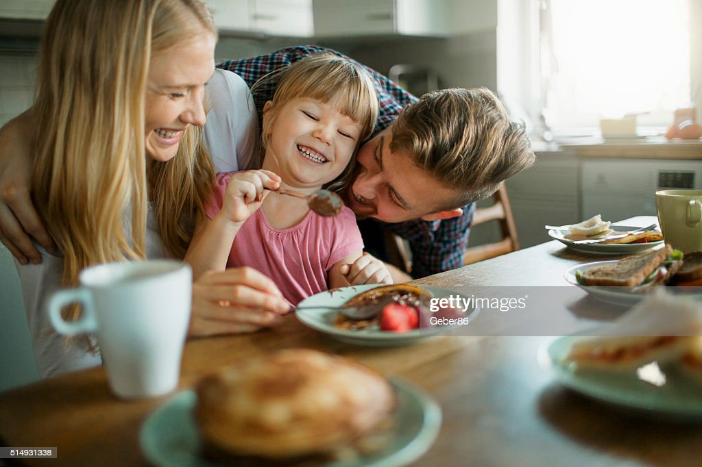 Photo of a young happy family having breakfast : Stock Photo