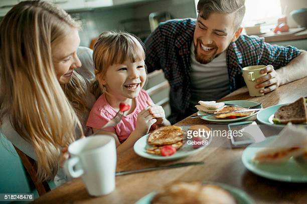 photo of a young happy family having breakfast - pancake stock pictures, royalty-free photos & images