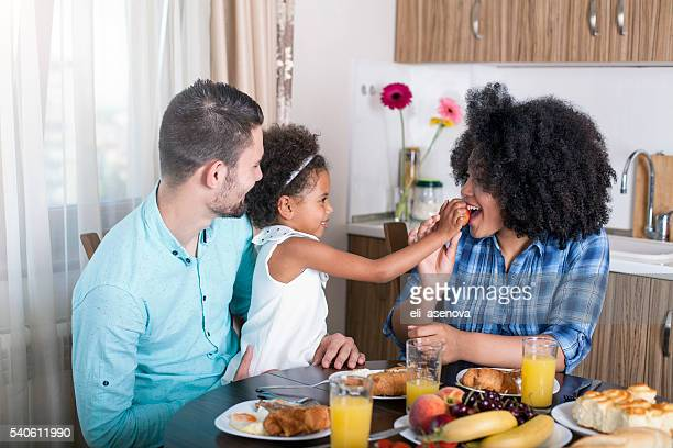 photo of a young happy family having breakfast - black family dinner stock photos and pictures