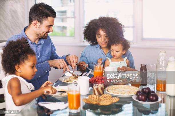 photo of a young happy family having breakfast - breakfast stock pictures, royalty-free photos & images