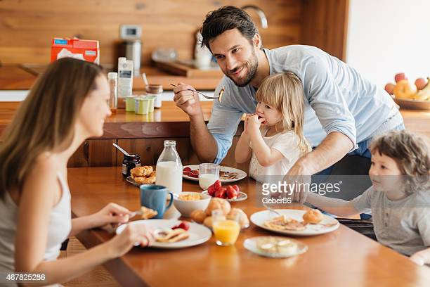 Photo of a young happy family having breakfast together