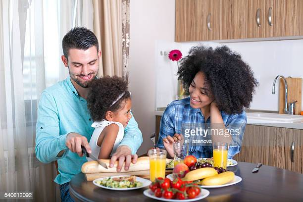 Photo of a young happy family sitting at dining table