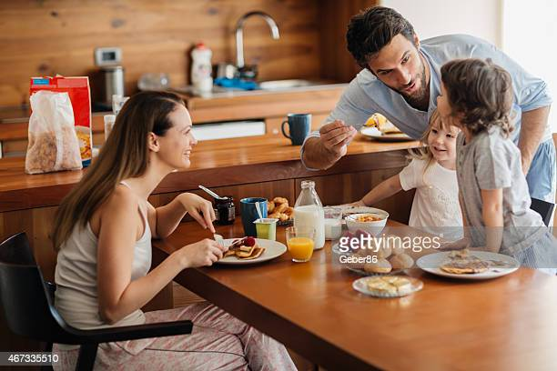 Photo of a young playful family having breakfast