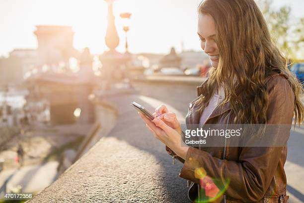 Photo of a young woman in big city holding smartphone
