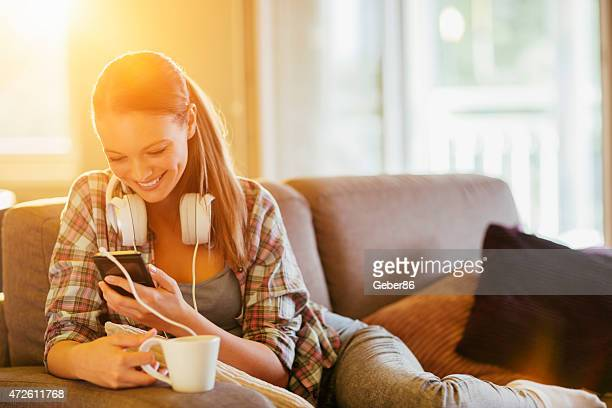 Photo of a young woman in sofa holding smartphone