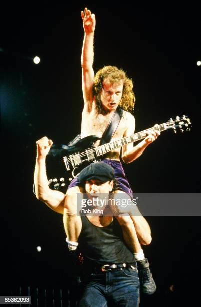 Photo of AC DC and Brian JOHNSON and Angus YOUNG and AC/DC Angus Young sitting on Brian Johnson's shoulders performing live onstage
