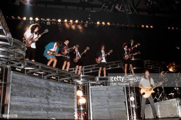 Photo of AC DC and Malcolm YOUNG and AC/DC Malcolm Young on stage with a host of Angus Young impersonators