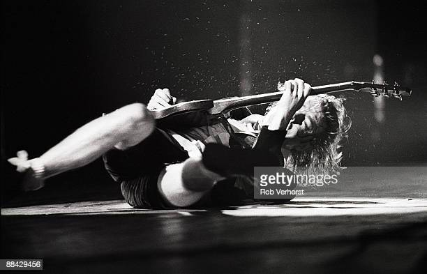 EDENHAL Photo of AC/DC and AC DC and Angus YOUNG Angus Young performing on stage lying down