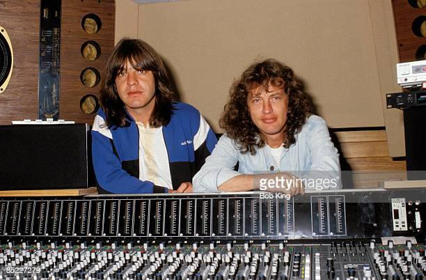 Photo of AC/DC and Malcolm YOUNG and Angus YOUNG and AC DC Malcolm Young and Angus Young posed behind mixing desk in recording studio c1987/1988