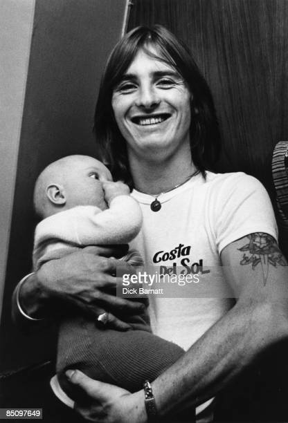Photo of AC/DC and Phil RUDD Portrait of Phil Rudd backstage with baby
