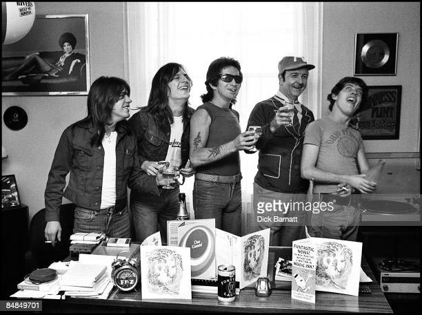 Photo of AC/DC LR Malcolm Young Mark Evans Bon Scott manager Michael Browning Angus Young posed at press reception in WEA offices