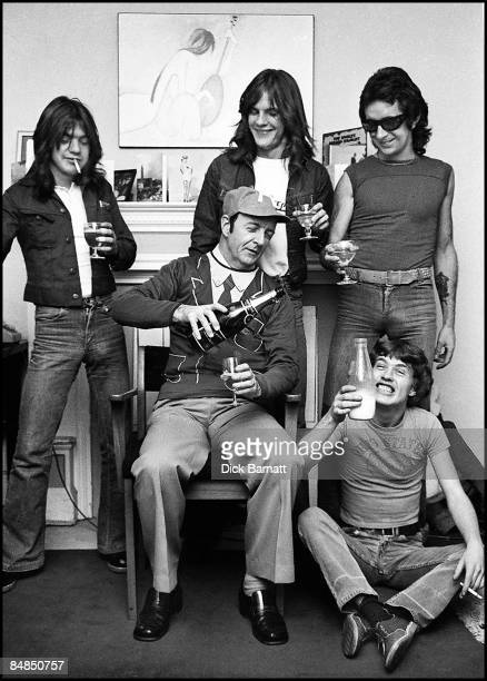 Photo of AC/DC LR Malcolm Young Mark Evans Bon Scott manager Michael Browning Angus Young drinking champagne at press reception in WEA offices