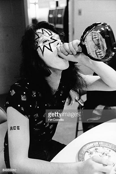 HALL Photo of Ace FREHLEY and KISS Ace Frehley posed backstage during cover session for Alive album drinking from bottle of Mateus Rose