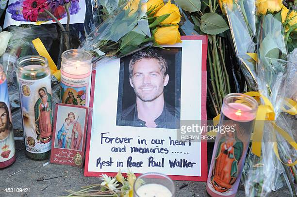 """Photo of actor Paul Walker is seen December 1, 2013 among flowers and candles left by fans at the site of the car accident in which the """"Fast and..."""