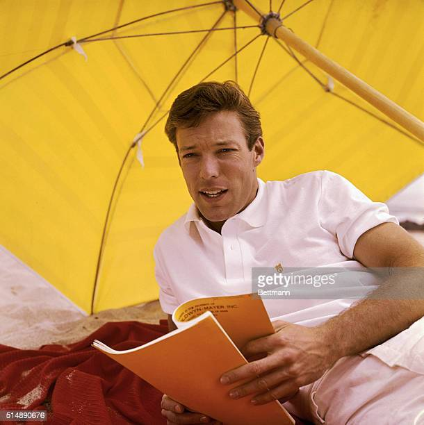Photo of actor Richard Chamberlain during the Dr Kildare years studying one of the television series' scripts on the beach under an umbrella ca 1960s