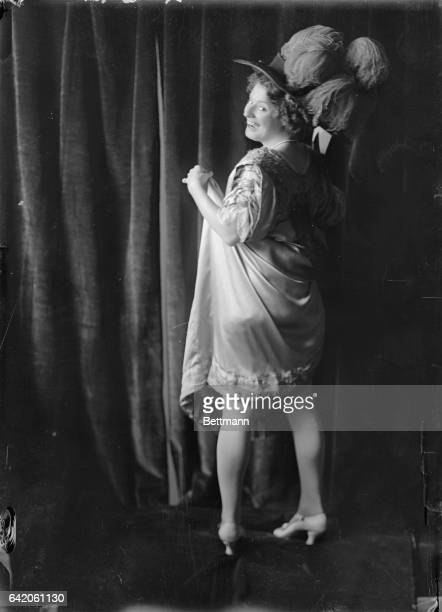 Photo of actress/singer Nora Bayes smiling with her back to the camera wearing a widebrimmed ostrichfeather hat