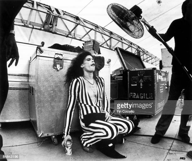 Photo of AEROSMITH lead singer Steven Tyler cools down with the aid of a large fan held by a roadie live at Washington RFK stadium