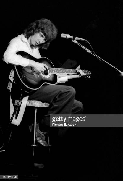 BOTTOMLINE Photo of Al STEWART Al Stewart performing on stage sitting on stool