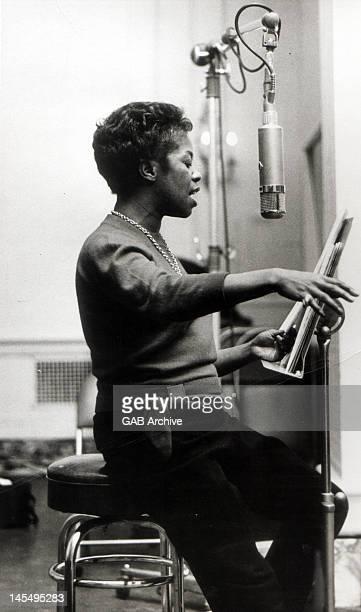 Circa 1960: Photo of American jazz singer Sarah Vaughan performing in a recording studio circa 1960.