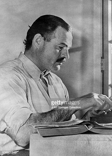Photo of American novelist Ernest Hemingway at work at his typewriter. Photograph taken in the 1930's.